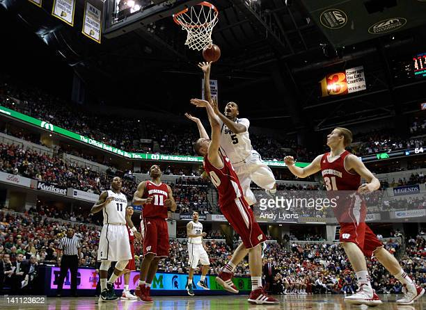Adreian Payne of the Michigan State Spartans drives for a shot attempt against Jared Berggren of the Wisconsin Badgers during their Semifinal game of...
