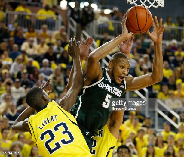 Adreian Payne of the Michigan State Spartans makes a first half pass around Caris LeVert of the Michigan Wolverines at Crisler Center on February 23...