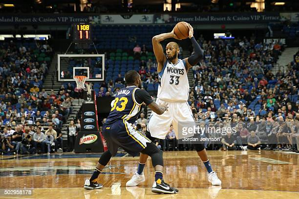 Adreian Payne of the Minnesota Timberwolves handles the ball against Trevor Booker of the Utah Jazz on December 30 2015 at Target Center in...