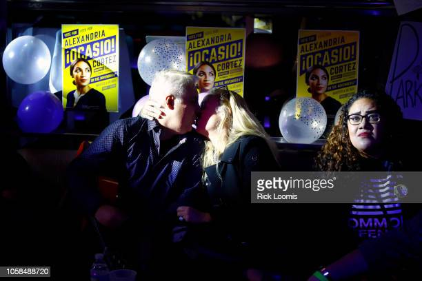 Adrian Acuardo kisses his wife Jennifer Cooper while watching election results come in on the large screen television at La Boom night club in Queens...