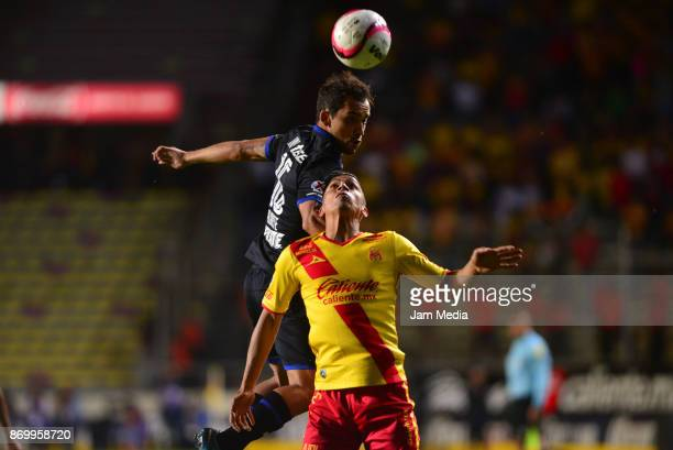Adrian Aldrete of Cruz Azul jumps over Angel Sepulveda of Morelia during the 16th round match between Morelia and Cruz Azul as part of the Torneo...