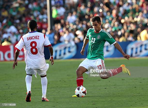 Adrian Aldrete of Mexico passes the ball past Marcos Sanchez of Panama during the first round of the 2013 CONCACAF Gold Cup at the Rose Bowl on July...