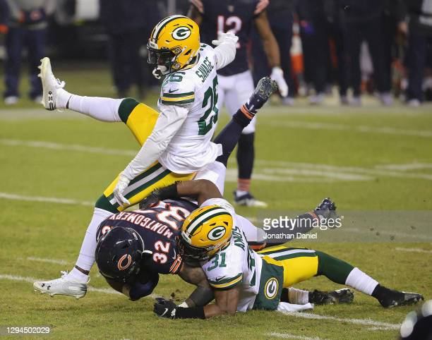 Adrian Amos and Darnell Savage of the Green Bay Packers bring down David Montgomery of the Chicago Bears at Soldier Field on January 03, 2021 in...