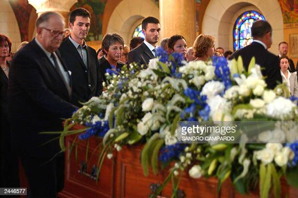 Adrian and Laurent de Mello stand between their mother, Annie and wife of Sergio Vieira de Mello as they look at the coffin containing containing his...