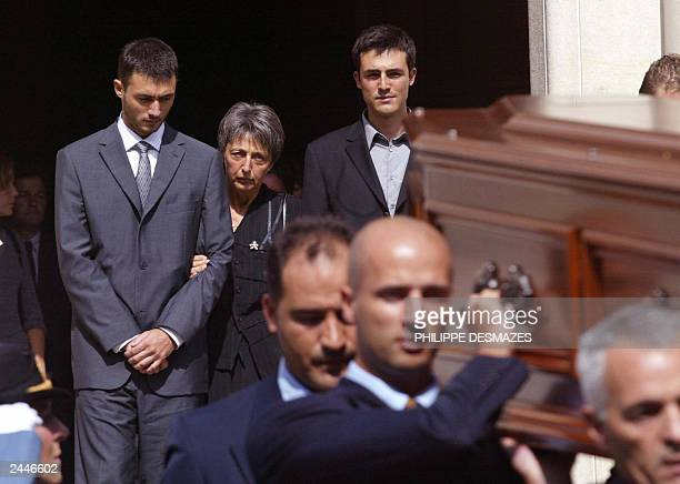 Adrian and Laurent de Mello stand between their mother Annie and wife of Sergio Vieira de Mello as they follow the coffin containing his body after...