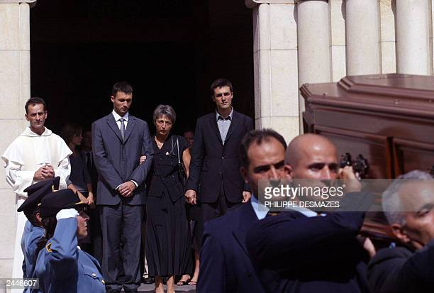 Adrian and Laurent de Mello stand between their mother, Annie and wife of Sergio Vieira de Mello, UN special envoy to Iraq as they follow the coffin...