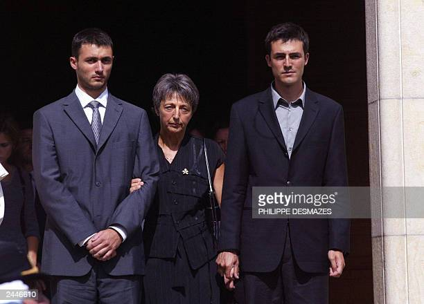 Adrian and Laurent de Mello stand between their mother Annie and wife of Sergio Vieira de Mello UN special envoy to Iraq as they walk out of church...