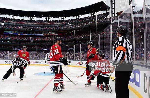 Adrian Aucoin of the Chicago Blackhawks skates to teammate Reid Simpson and Reggie Kerr to celebrate during the 2017 Bridgestone NHL Winter Classic...