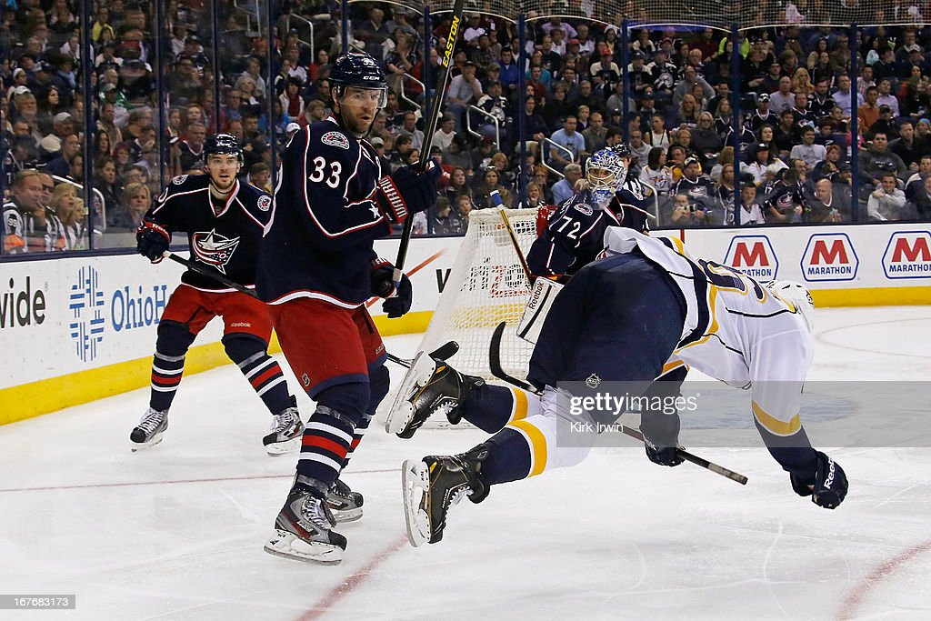 Adrian Aucoin #33 of the Columbus Blue Jackets knocks down Kevin Henderson #46 of the Nashville Predators while battling for control of a loose puck during the third period on April 27, 2013 at Nationwide Arena in Columbus, Ohio. Columbus defeated Nashville 3-1.