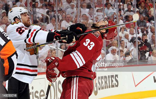 Adrian Aucoin of the Phoenix Coyotes takes a punch from Viktor Stalberg of the Chicago Blackhawks in Game Five of the Western Conference...