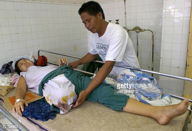 Adrian Bagasala attends to his wife Ivy who had to have her leg amputated in a government hospital in Legazpi city 03 December 2006 when their home...