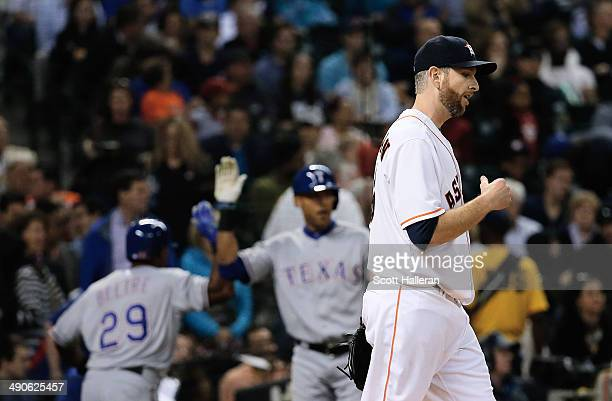 Adrian Beltre and Alex Rios of the Texas Rangers celebrate after Beltre scored a run in the fifth inning as Scott Feldman of the Houston Astros looks...