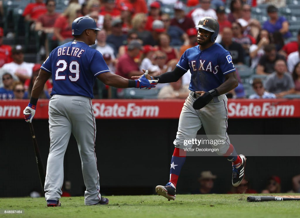 Adrian Beltre #29 and Delino DeShields #3 of the Texas Rangers celebrate after DeShields scored on a sacrifice fly during the eighth inning of the MLB game against the Los Angeles Angels of Anaheim at Angel Stadium of Anaheim on September 17, 2017 in Anaheim, California. The Rangers defeated the Angels 402.