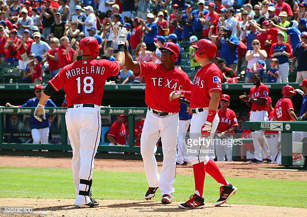 Adrian Beltre of the Texas Rangers and Ryan Rua congratulates Mitch Moreland for hitting a three run home run in the fourth inning against the...