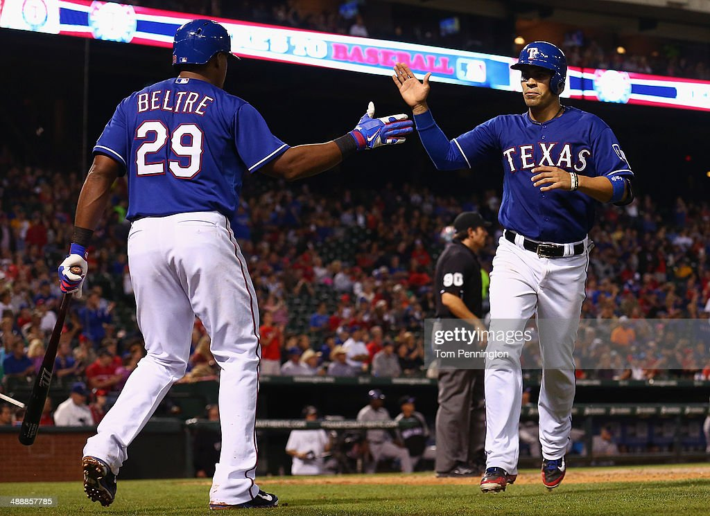 Adrian Beltre #29 of the Texas Rangers celebrates with Robinson Chirinos #61 of the Texas Rangers after Chirinos scored against the Colorado Rockies in the bottom of the seventh inning at Globe Life Park in Arlington on May 8, 2014 in Arlington, Texas.