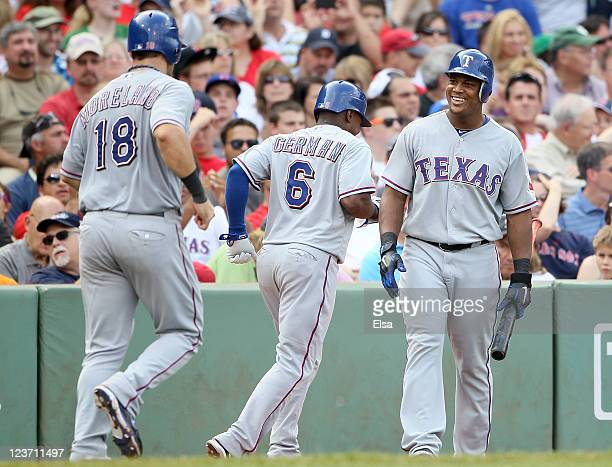 Adrian Beltre of the Texas Rangers congratulates teammates Esteban German and Mitch Moreland after they scored on a triple hit by Josh Hamilton in...