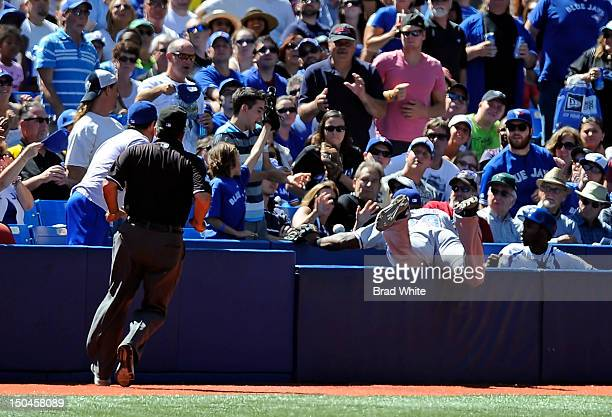 Adrian Beltre of the Texas Rangers dives into the crowd chasing a foul ball as Third Base Umpire Tim Tschida looks to make the call during MLB game...