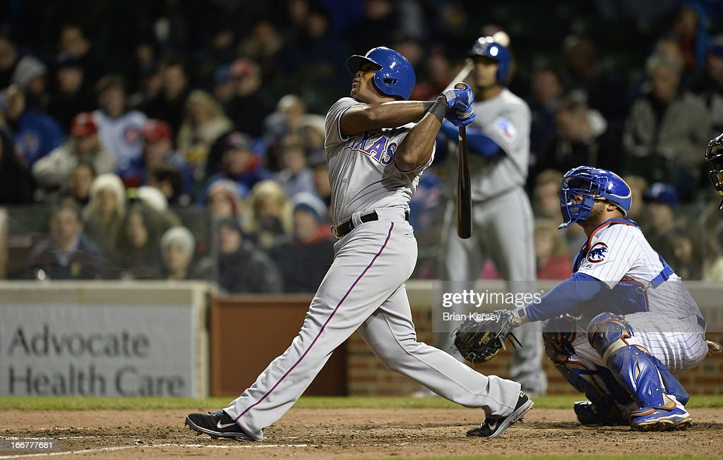 Adrian Beltre of the Texas Rangers (L) follows through on a two-run home run, scoring Elvis Andrus as Welington Castillo of the Chicago Cubs catches in the eighth inning at Wrigley Field on April 16, 2013 in Chicago, Illinois. All uniformed team members are wearing jersey number 42 in honor of Jackie Robinson Day.