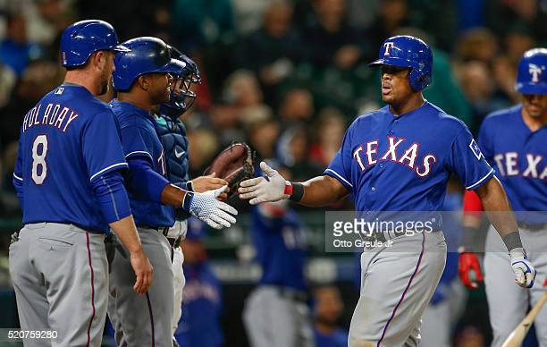 Adrian Beltre of the Texas Rangers is congratulated by teammates after hitting a threerun homer against the Seattle Mariners in the third inning at...