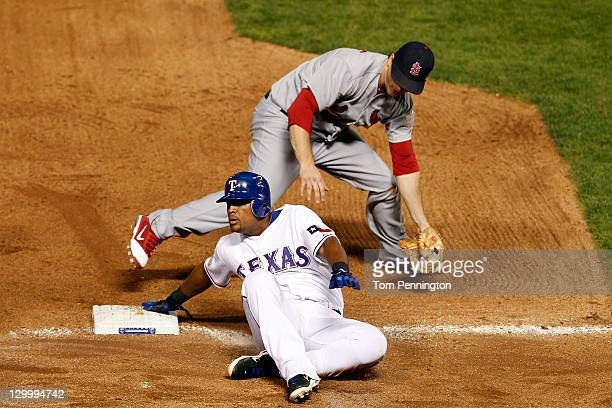 Adrian Beltre of the Texas Rangers is safe at third base after the tag by Ryan Theriot of the St Louis Cardinals in the seventh inning during Game...