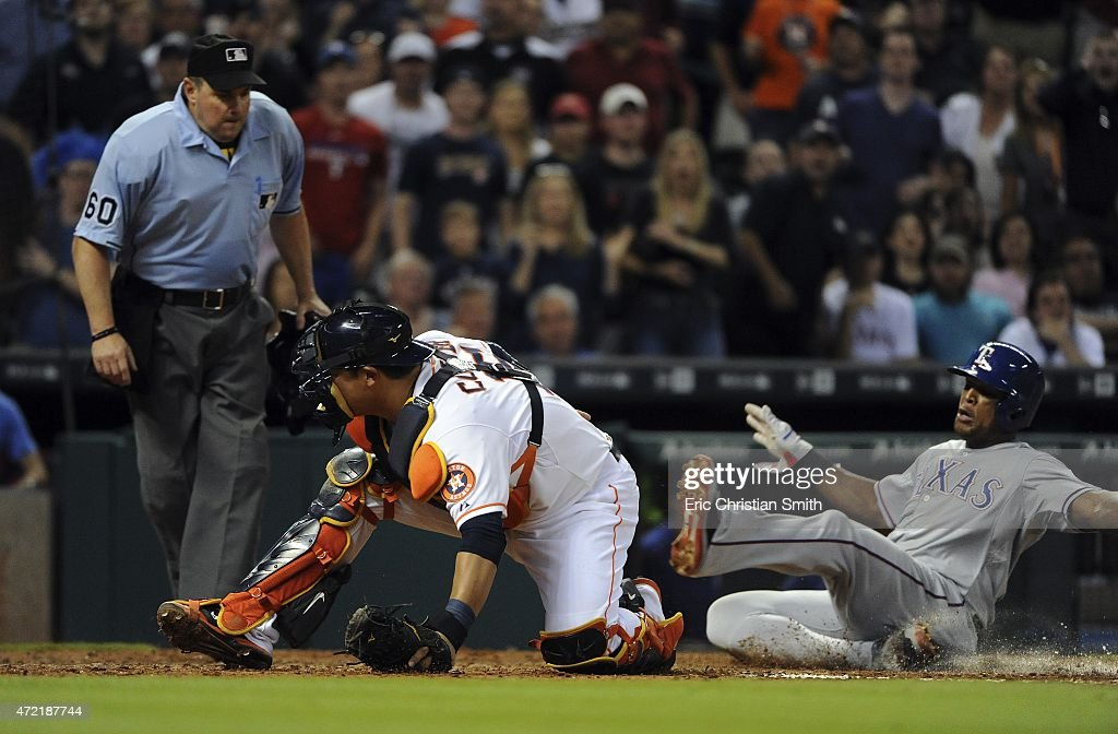 Adrian Beltre #29 of the Texas Rangers, right, scores the go-ahead run past Hank Conger #16 of the Houston Astros during the ninth inning at Minute Maid Park on May 4, 2015 in Houston, Texas.