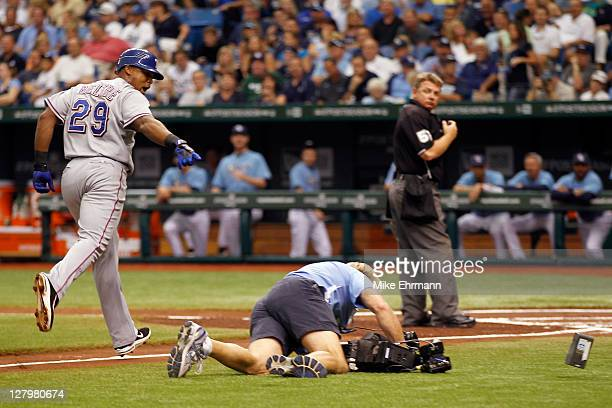 Adrian Beltre of the Texas Rangers rounds the bases and points at a TBS cameraman who falls on his way to video Beltre at home plate after Beltre...