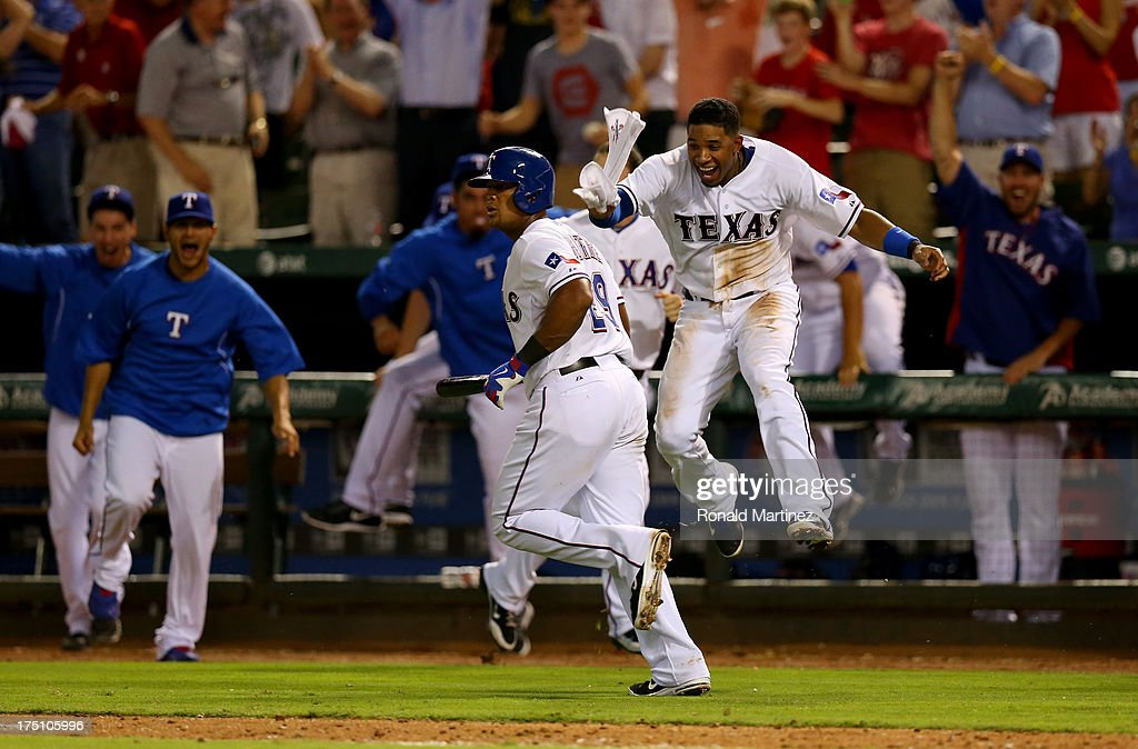 Adrian Beltre #29 of the Texas Rangers runs the bases while Elvis Andrus #1 celebrate his walk off homerun against the Los Angeles Angels at Rangers Ballpark in Arlington on July 31, 2013 in Arlington, Texas.