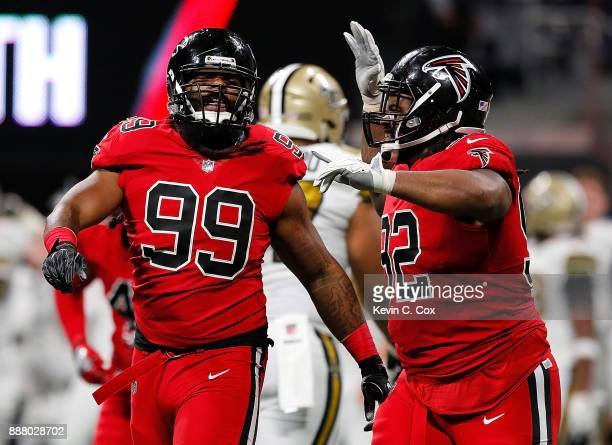 Adrian Clayborn of the Atlanta Falcons reacts with Dontari Poe after sacking Drew Brees of the New Orleans Saints at Mercedes-Benz Stadium on...