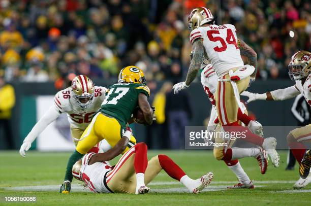 Adrian Colbert and Reuben Foster of the San Francisco 49ers tackle Davante Adams of the Green Bay Packers during the game at Lambeau Field on October...