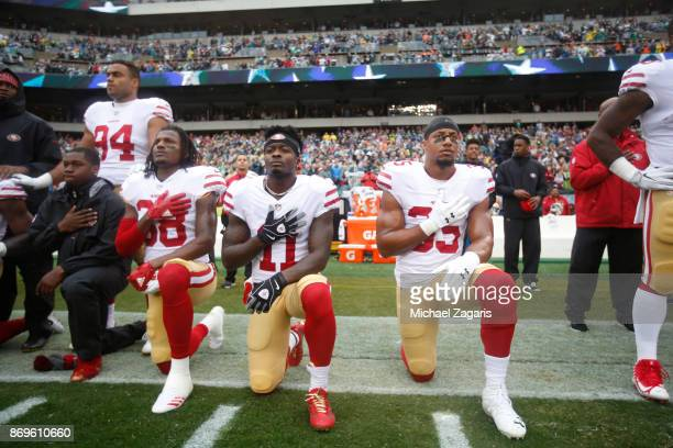 Adrian Colbert Marquise Goodwin and Eric Reid of the San Francisco 49ers kneel during the anthem prior to the game against the Philadelphia Eagles at...