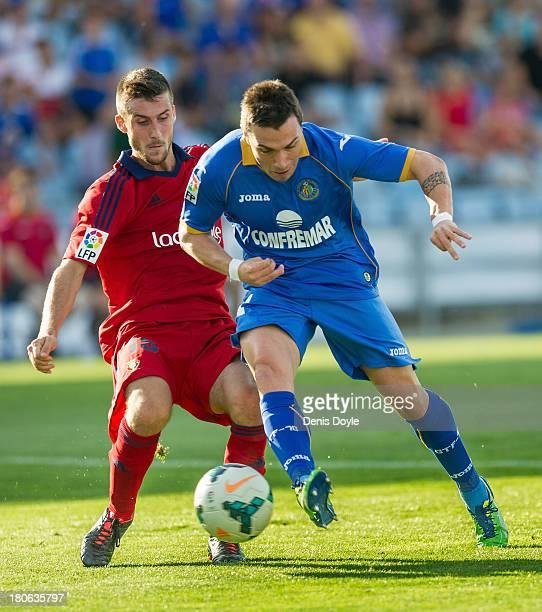 Adrian Colunga of Getafe battles for the ball with Oier Sanjurjo of Osasuna during the La Liga match between Getafe CF v CA Osasuna at Coliseum...