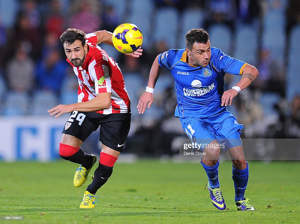 Adrian Colunga (R) of Getafe CF battles for the ball against Mikel Belenziaga of Athletic Club during the La Liga match between Getafe CF and Athletic Club at Coliseum Alfonso Perez stadium on October 28, 2013 in Getafe, Spain.