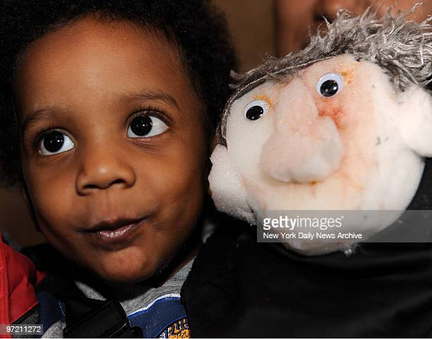 Adrian Cooper 22 mos with his hand made puppet made by him with the help of Lucrecia Novoa during her visit to teach neighborhood families how to...