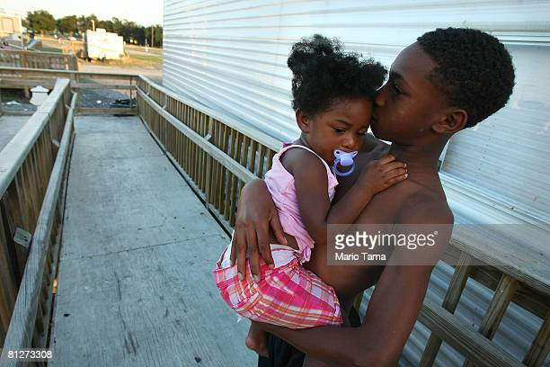 Adrian Cross holds his sister Kailah Smith 18 months outside their parents' trailer just before the family moved out of the trailer in FEMA Diamond...