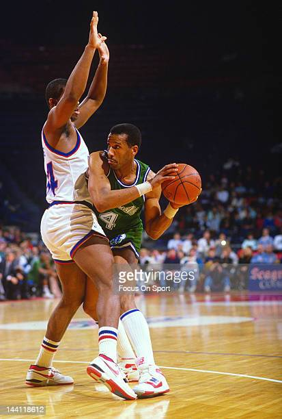 Adrian Dantley of the Dallas Mavericks is guarded closely by John Williams of the Washington Bullets during an NBA basketball game circa 1989 at the...