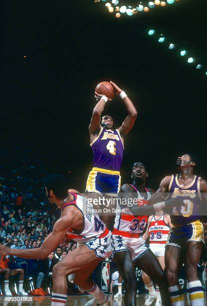Adrian Dantley of the Los Angeles Lakers shoots over Greg Ballard and Larry Wright of the Washington Bullets during an NBA basketball game circa 1978...