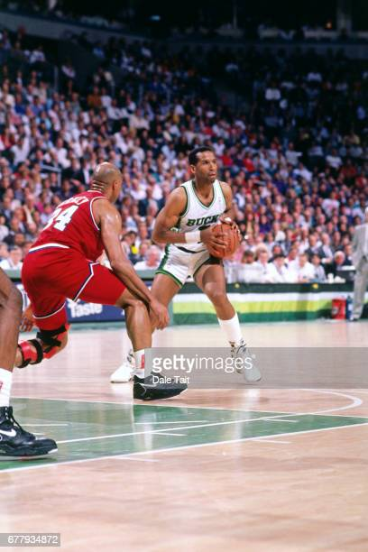 Adrian Dantley of the Milwaukee Bucks passes against Charles Barkley of the Philadelphia 76ers circa 1990 at Bradley Center in Milwaukee Wisconsin...
