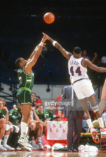 Adrian Dantley of the Milwaukee Bucks shoots over Harvey Grant of the Washington Bullets during an NBA basketball game circa 1991 at the Capital...