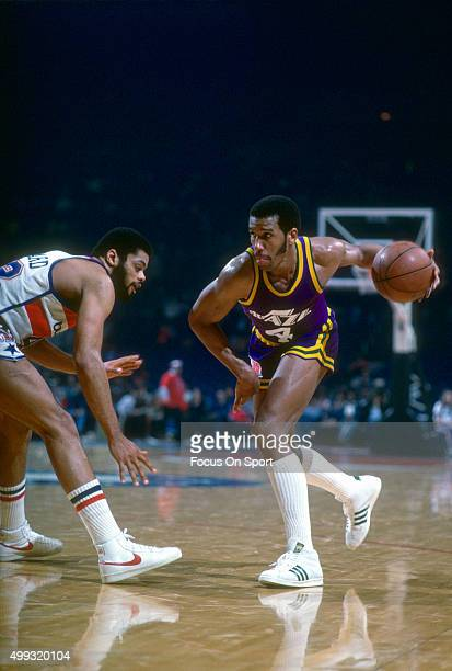 Adrian Dantley of the Utah Jazz dribbles past Greg Ballard of the Washington Bullets during an NBA basketball game circa 1980 at the Capital Centre...