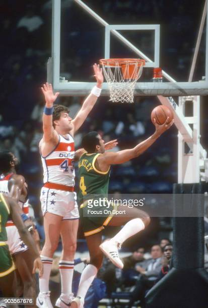 Adrian Dantley of the Utah Jazz goes up to shoot over Jeff Ruland of the Washington Bullets during an NBA basketball game circa 1982 at the Capital...