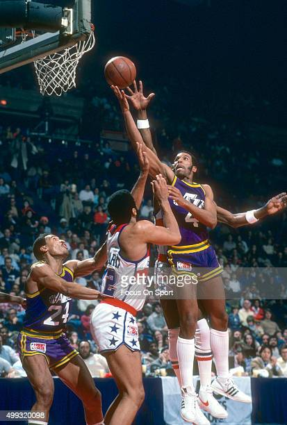 Adrian Dantley of the Utah Jazz looks to shoot over Greg Ballard of the Washington Bullets during an NBA basketball game circa 1980 at the Capital...