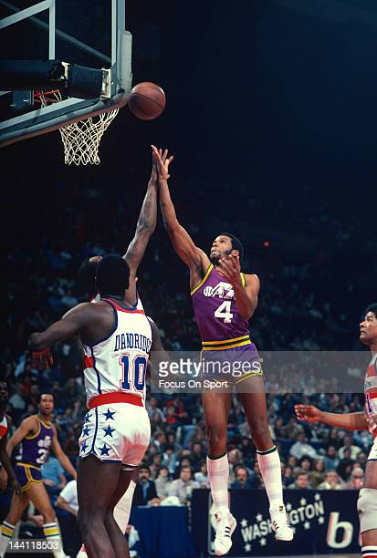 Adrian Dantley of the Utah Jazz shoots over Elvin Hayes and Bob Dandridge of the Washington Bullets during an NBA basketball game circa 1981 at the...