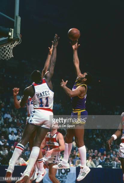 Adrian Dantley of the Utah Jazz shoots over Elvin Hayes and Greg Ballard of the Washington Bullets during an NBA basketball game circa 1981 at the...