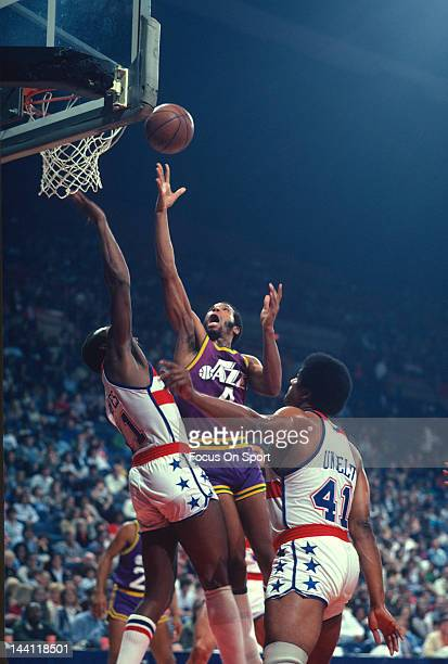 Adrian Dantley of the Utah Jazz shoots over Elvin Hayes and Wes Unseld of the Washington Bullets during an NBA basketball game circa 1981 at the...