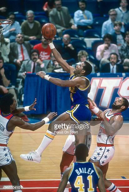 Adrian Dantley of the Utah Jazz shoots over Greg Ballard of the Washington Bullets during an NBA basketball game circa 1984 at the Capital Centre in...