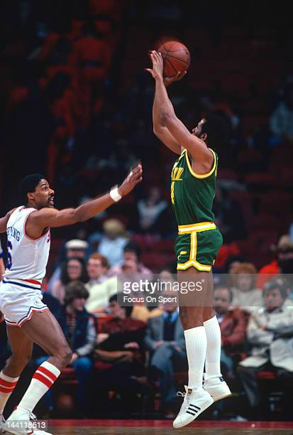 Adrian Dantley of the Utah Jazz shoots over Julius Erving of the Philadelphia 76ers during an NBA basketball game circa 1984 at The Spectrum in...
