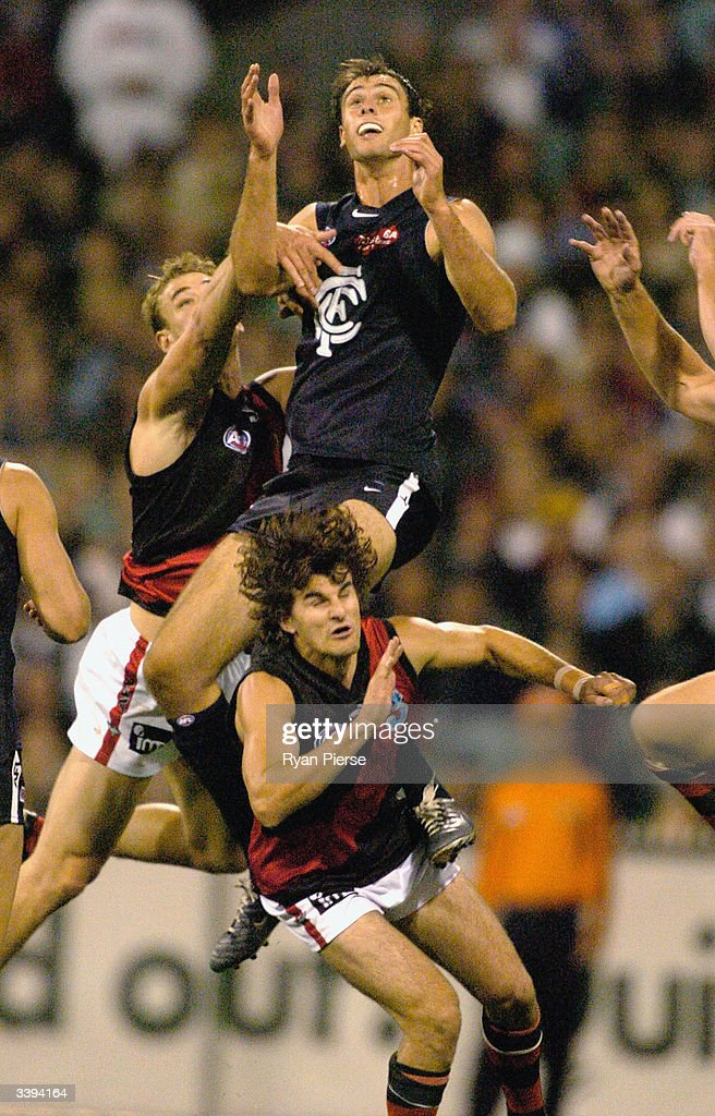 Adrian Deluca #26 for the Blues flys over Damien Peverill #11 for the Bombers during the round four AFL match between The Carlton Blues and the Essendon Bombers at the M.C.G. on April 16, 2004 in Melbourne, Australia.