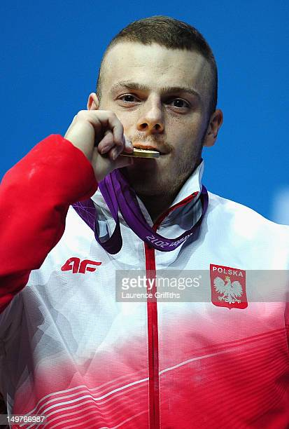 Adrian Edward Zielinski of Poland celebrates on the podium after winning the Gold medal following the Men's 85kg Weightlifting Final on Day 7 of the...