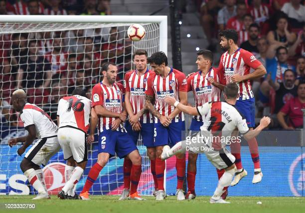 Adrian Embarba of Rayo Vallecano de Madrid shoots a free kick over the Atletico wall during the La Liga match between Club Atletico de Madrid and...