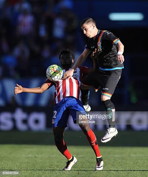 Adrian Embarba of Rayo Vallecano tackles Thomas Partey of Club Atletico de Madrid during the La Liga match between Club Atletico de Madrid and Rayo...